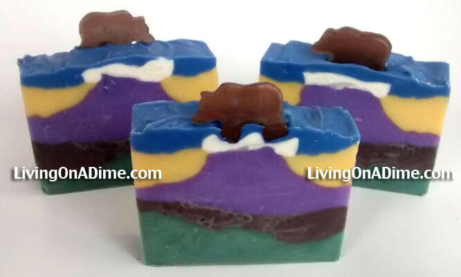 This homemade soap is my Rocky Mountain lye soap. It's inspired by the mountain beauty here in Colorado. This is a pretty advanced lye soap to make. You have to wait for each layer to set up before putting the next layer on and then you have to carefully pile the soap in the middle to make the mountain. Then you put a different color on the sides to hold up your mountain. The little bears on top are made of melt and pour soap poured into a bear silicone mold.