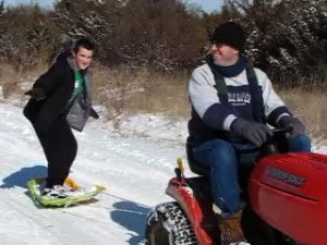 snow surfing behind a lawn mower